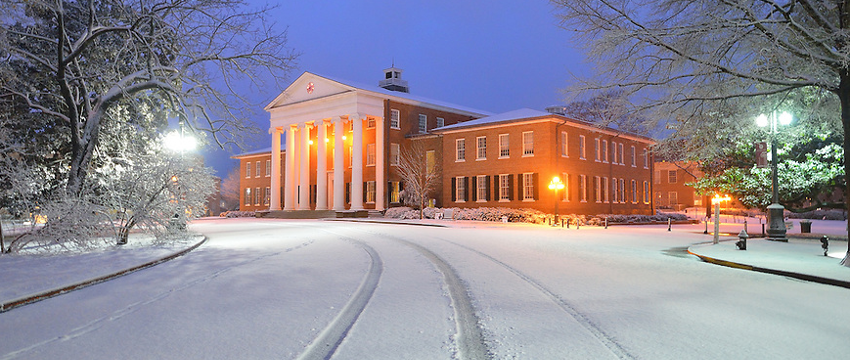 Lyceum at dusk, snow on the ground imprinted with tire tracks